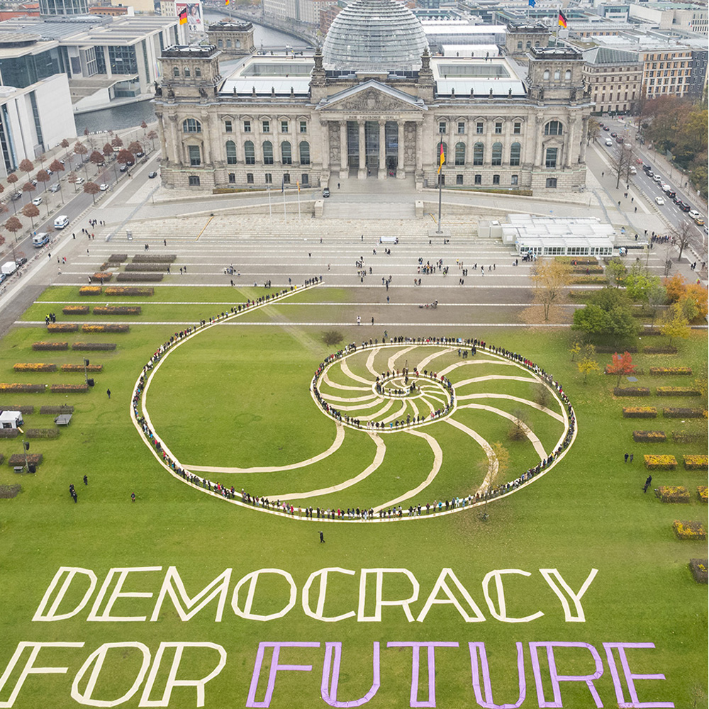 On the lawn in front of the Reichstag, people form a chain to the entrance of the building, which symbolically represents the transfer of the recommendations of the citizens' council from people to politics.