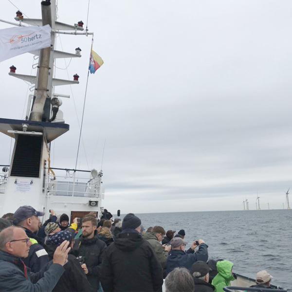 Menschen auf einem Boot, im Hintergrund ein offshore Windpark