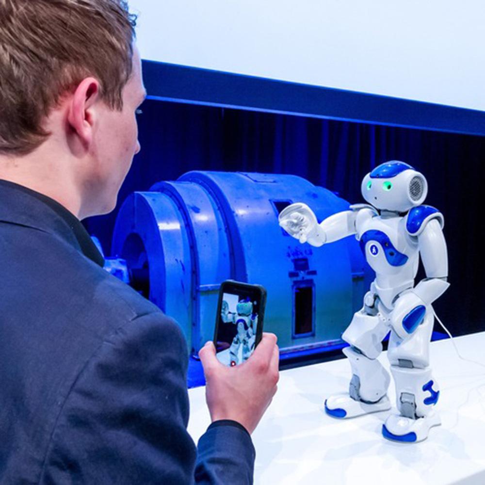 Ein Besucher interagiert mit einem Roboter.