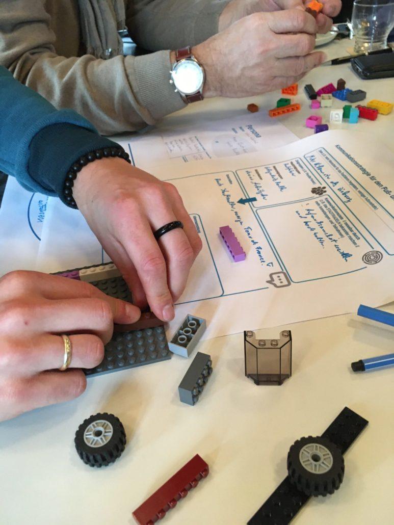 Es sind die Hände zweier Menschen zu sehen, die mit Lego Formen gestalten.