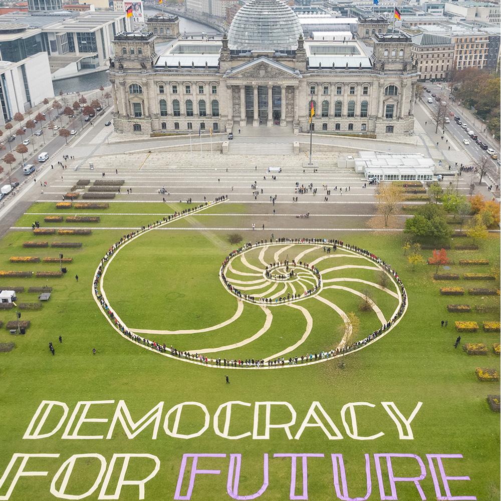 Auf der Wiese vor dem Reichstag bilden Menschen eine Kette bis zum Eingang des Gebäudes, die symbolisch die Übergabe der Empfehlungen des Bürgerrats von den Menschen an die Politik darstellt.