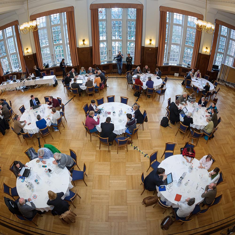 An 10 Tischen verteilt diskutieren je 4-6 Teilnehmende, unterstützt durch je eine*n Tischmoderator*in.