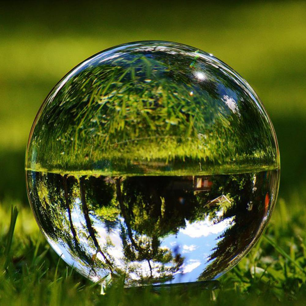 Eine auf Rasen liegende Glaskugel reflektiert Himmel, Bäume und Gräser