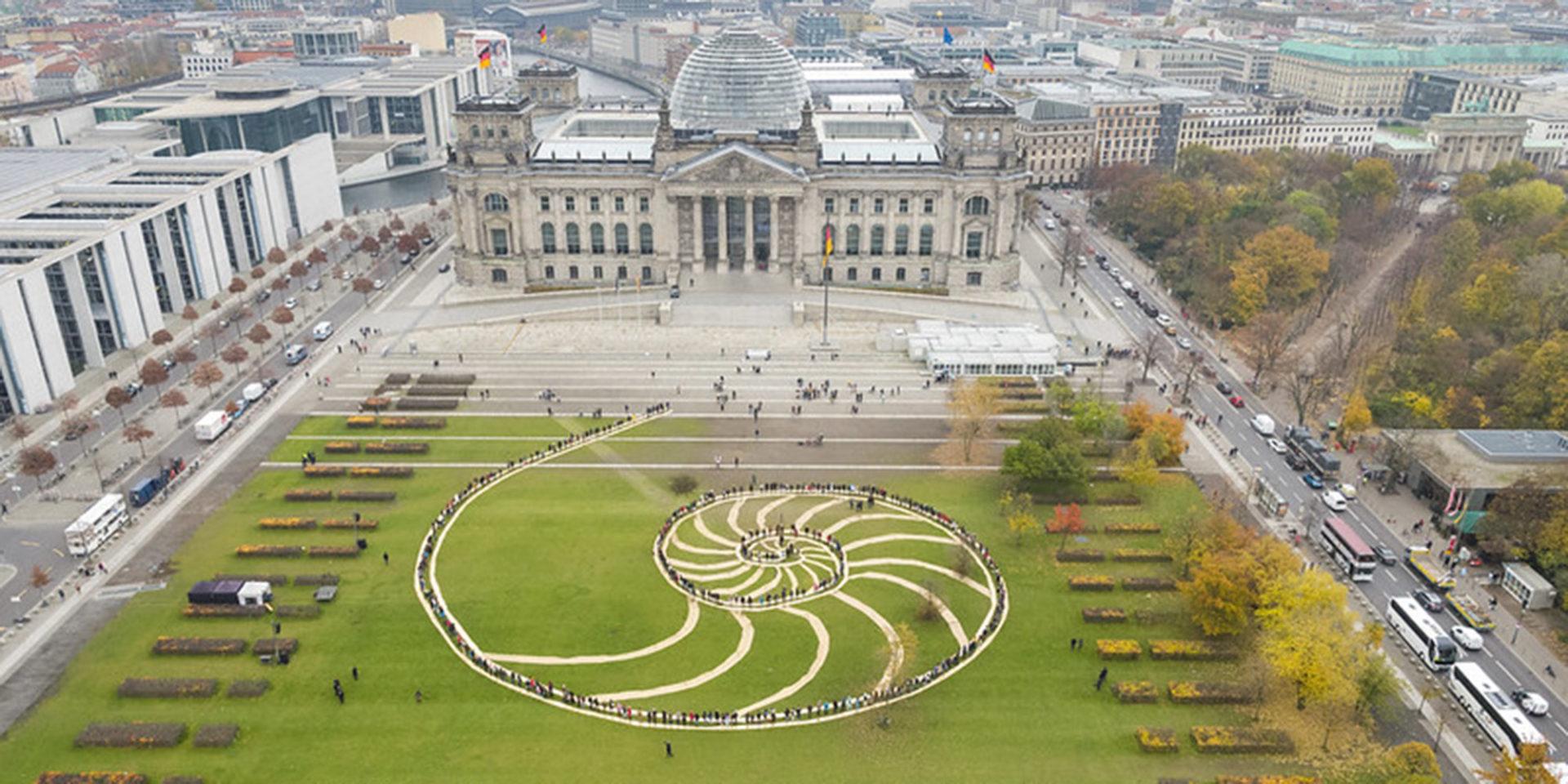 """Die Luftaufnahme zeigt den Reichstag in Berlin mit der davor liegenden Wiese, auf dieser ist der Schriftzug """"Democracy for Future"""" zu lesen."""