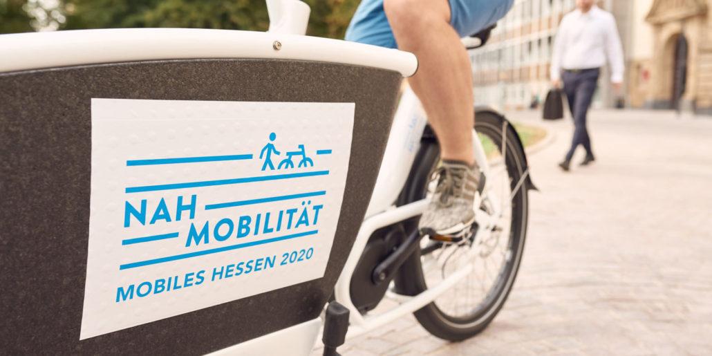 """Ein Mann sitzt auf einem Fahrrad, welches die Aufschrift """"Nah Mobilität Mobiles Hessen 2020"""" trägt."""