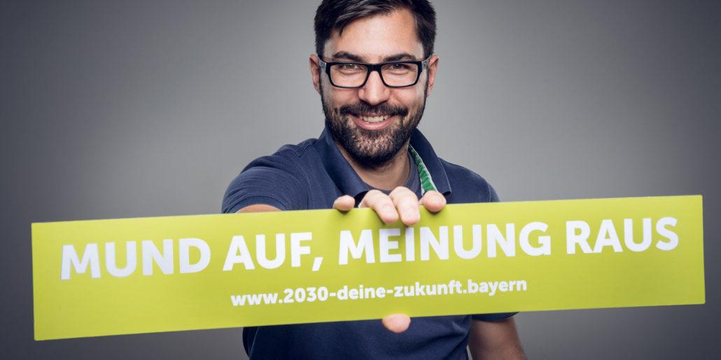 """Ein Mann hält einen Banner mit dem Schriftzug """"Mund auf, Meinung raus - www.2030-deine-zukunft.bayern"""" in der Hand"""