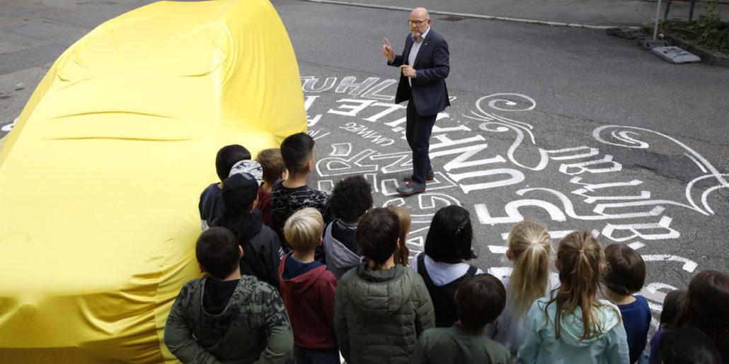 Eine Gruppe von Kindern steht auf einer mit Kreide bemalten Straße und hört einem Mann in Anzug zu - neben der Gruppe ist ein mit einem gelben Tuch verdecktes Auto zu sehen.