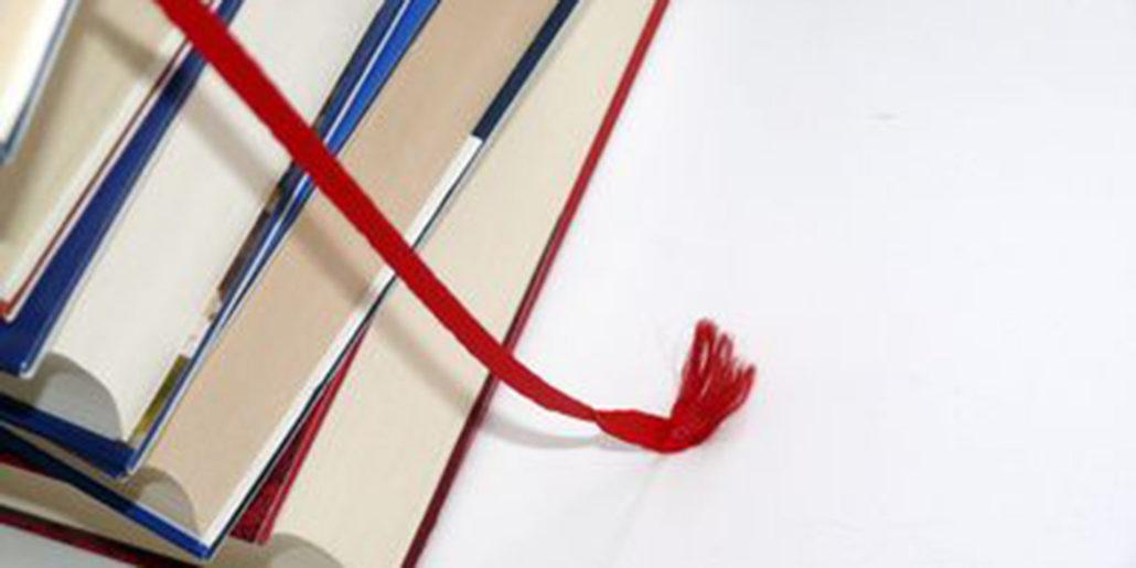 Ein Ausschnitt eines Bücherstapels mit einem roten Lesezeichen im Fokus.