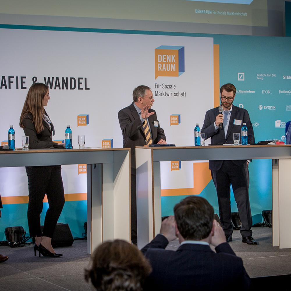 Teilnehmerinnen und Teilnehmer der Veranstaltung sitzen im Plenum, auf der Bühne sprechen die zwei Moderator*innen.