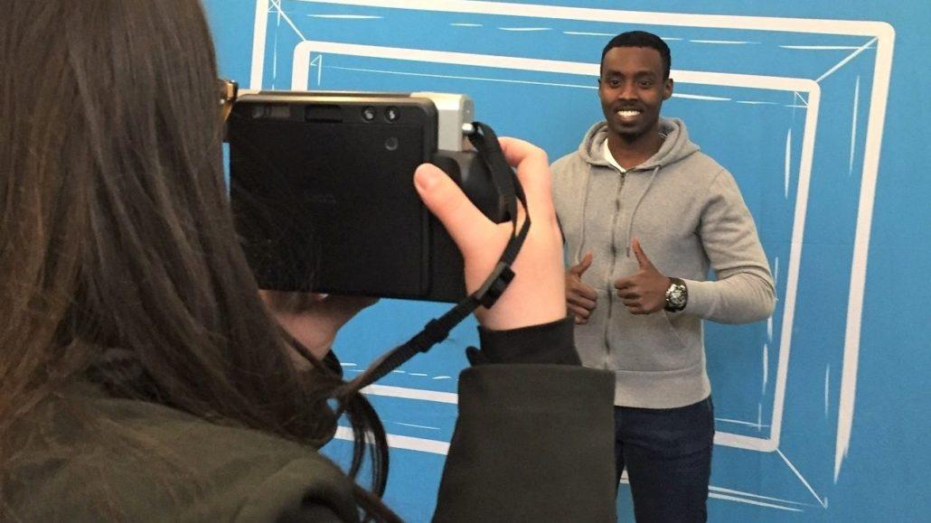 Ein Mann wird vor einer blauen Hintergrundwand fotografiert.