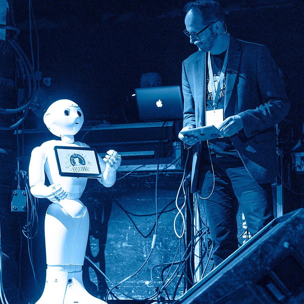 Moderator und Roboter stehen gemeinsam auf der Bühne des Enabling Innovation Festivals in Münster, 2019.