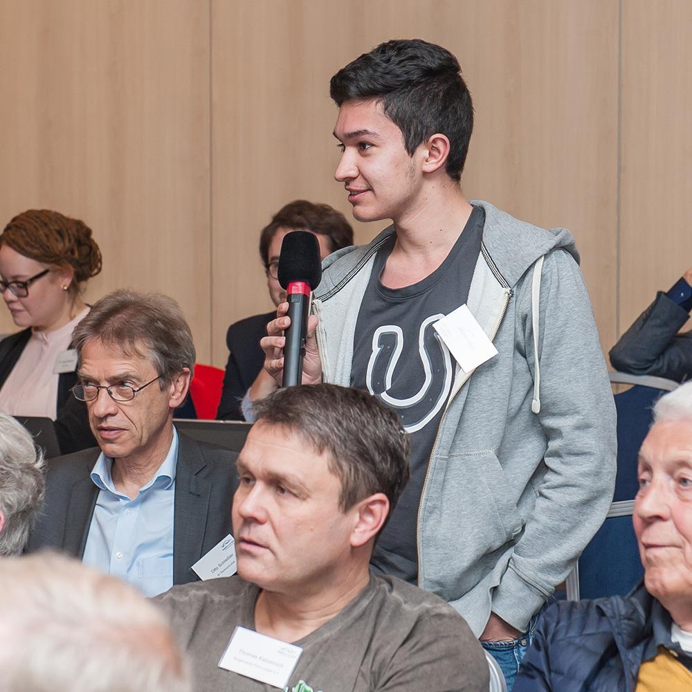 Ein Jugendlicher teilt stehen deinen Wortbeitrag mit Mikrofon, um ihn herum sitzen andere Teilnehmende in Reihen.