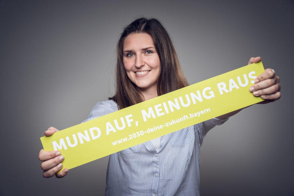 """Eine Frau hält einen Banner mit dem Schriftzug """"Mund auf, Meinung raus - www.2030-deine-zukunft.bayern"""" in der Hand"""