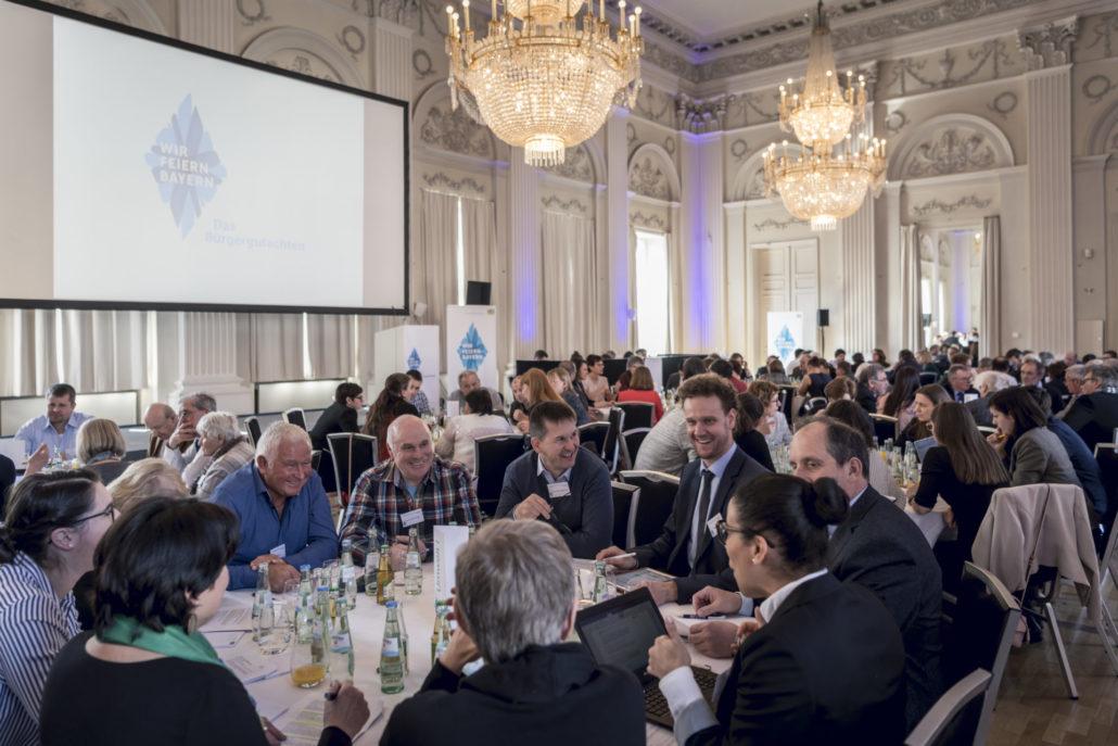 In einem repräsentativen Veranstaltungsraum mit hohen Decken und Kronleuchtern sitzen die Teilnehmenden an runden Diskussionstischen.