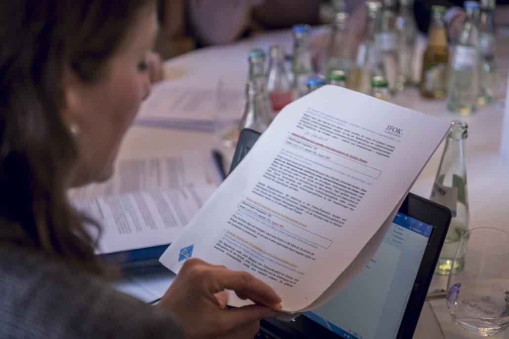 Eine Dialogteilnehmerin sitzt vertieft in Veranstalungsmaterial in Papier- und digitaler Form an einem der runden Tische.