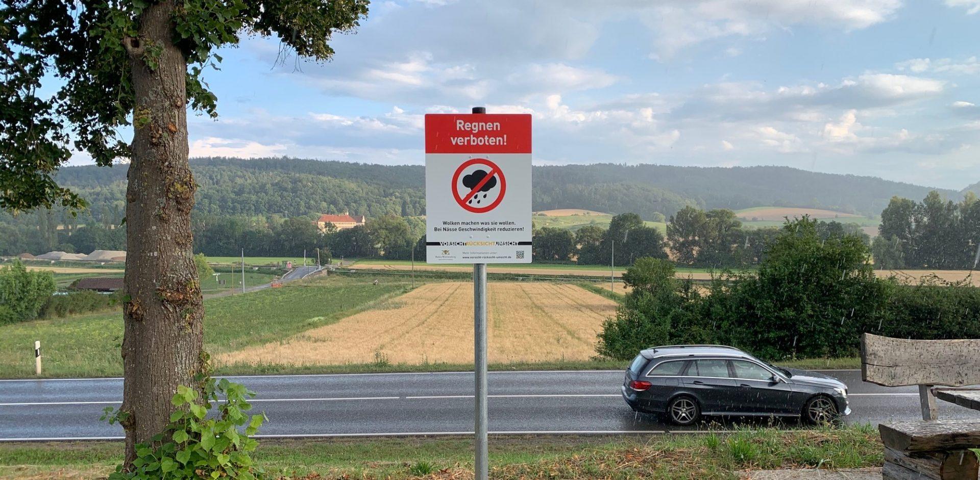 """Foto eines Schildes mit dem Aufdruck """"Regnen verboten"""", im Hintergrund eine Landstraße mit fahrenden Autos bei Regen"""