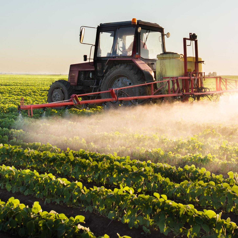 Ein Landwirt fährt mit seinem Traktor über ein Feld und wässert.