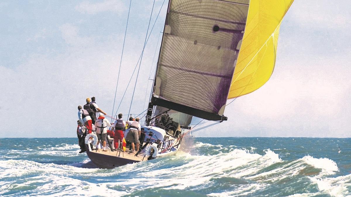 Eine Crew auf einem Segelschiff hisst die Segel