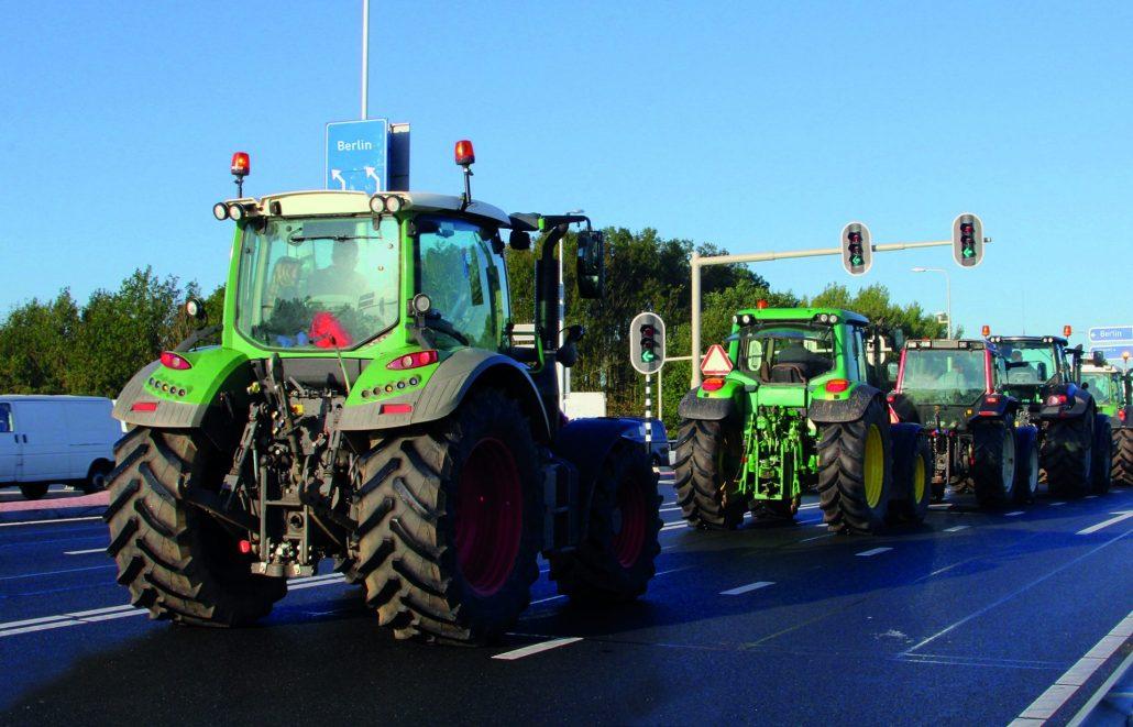 Mehrere Traktoren fahren hintereinander eine Straße entlang.
