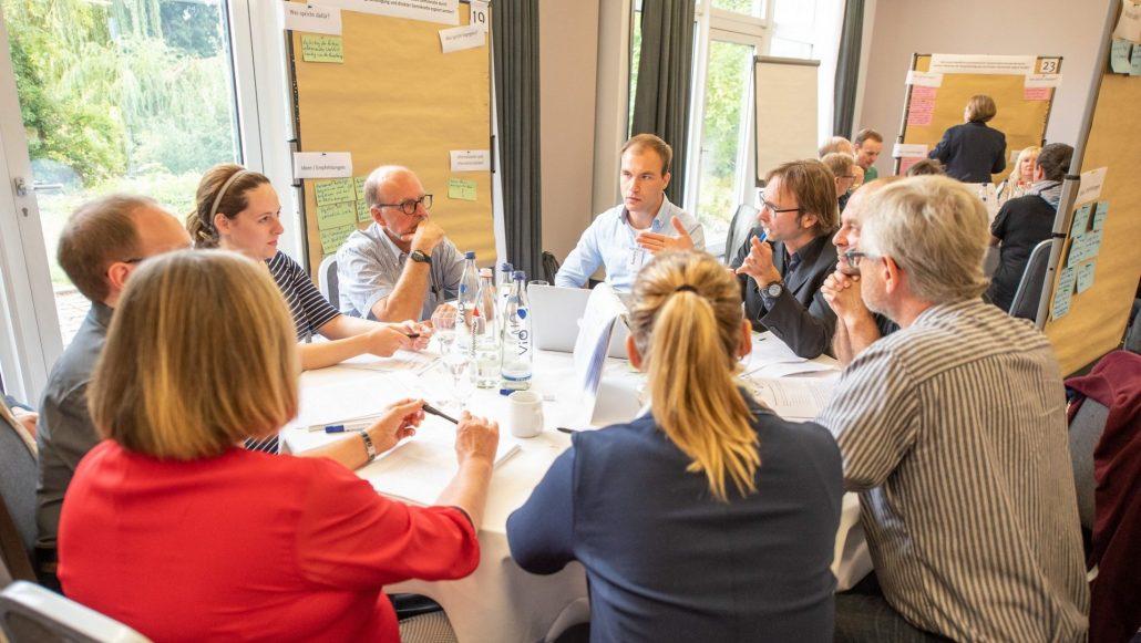 Sieben Bürgerinnen und Bürger unterschiedlichen Alters, Geschlechts und Herkunft sitzen um einen runden Tisch und diskutieren angeleitet von einem Moderator und beobachtet von einem Protokollanten.