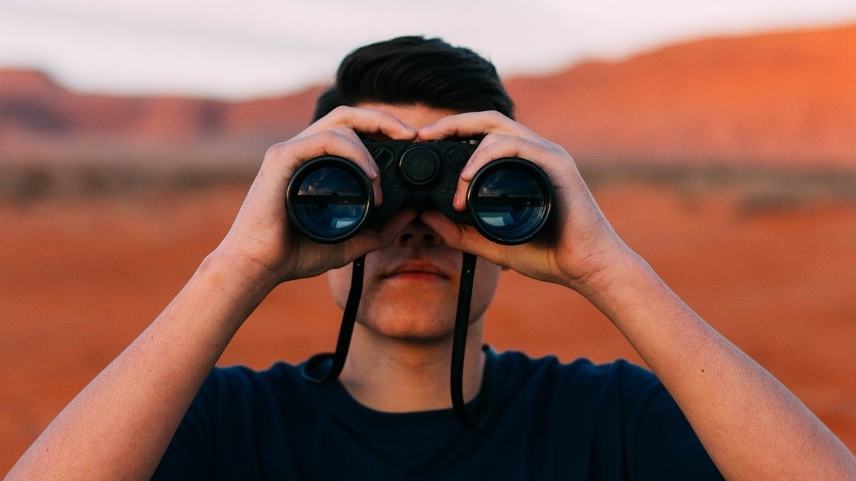 Ein junger Mann schaut in einer wüstenartigen Umgebung durch ein Fernglas.