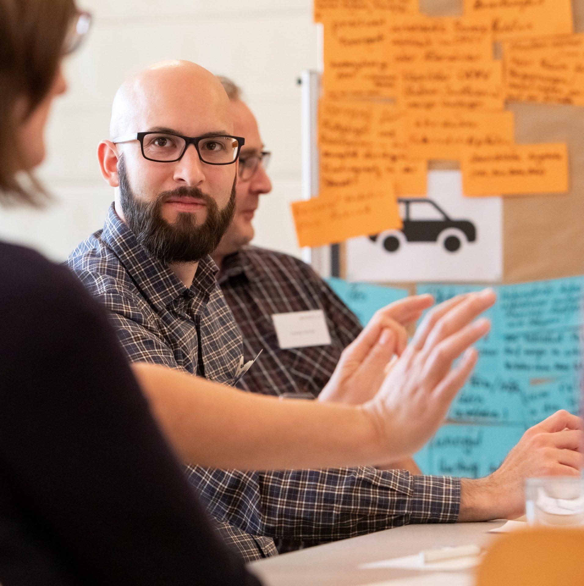Teilnehmende an einem Beteiligungsformat diskutieren