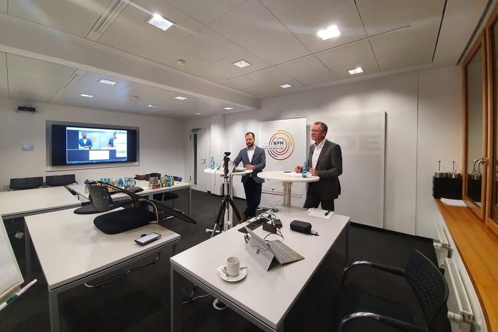Ein Webinar der NPM mit zwei Personen vor Ort und den übrigen Teilnehmer:innen virtuell zugeschaltet.