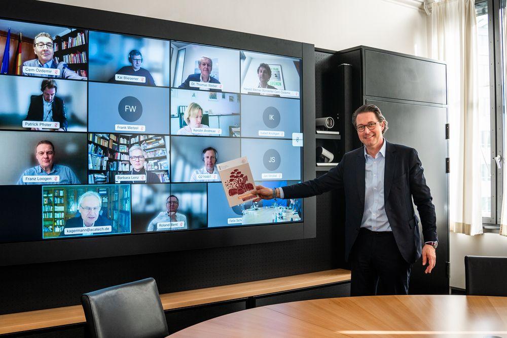 Bundesverkehrsminister Andreas Scheuer mit dem Fortschrittsbericht der NPM vor einer Leinwand mit Teilnehmenden einer Videokonferenz.