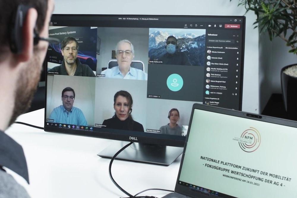 Das Setting einer virtuellen Arbeitsgruppensitzung ist zu sehen. Eine Person vor dem Bildschirm, dort eine Videkonferenz.