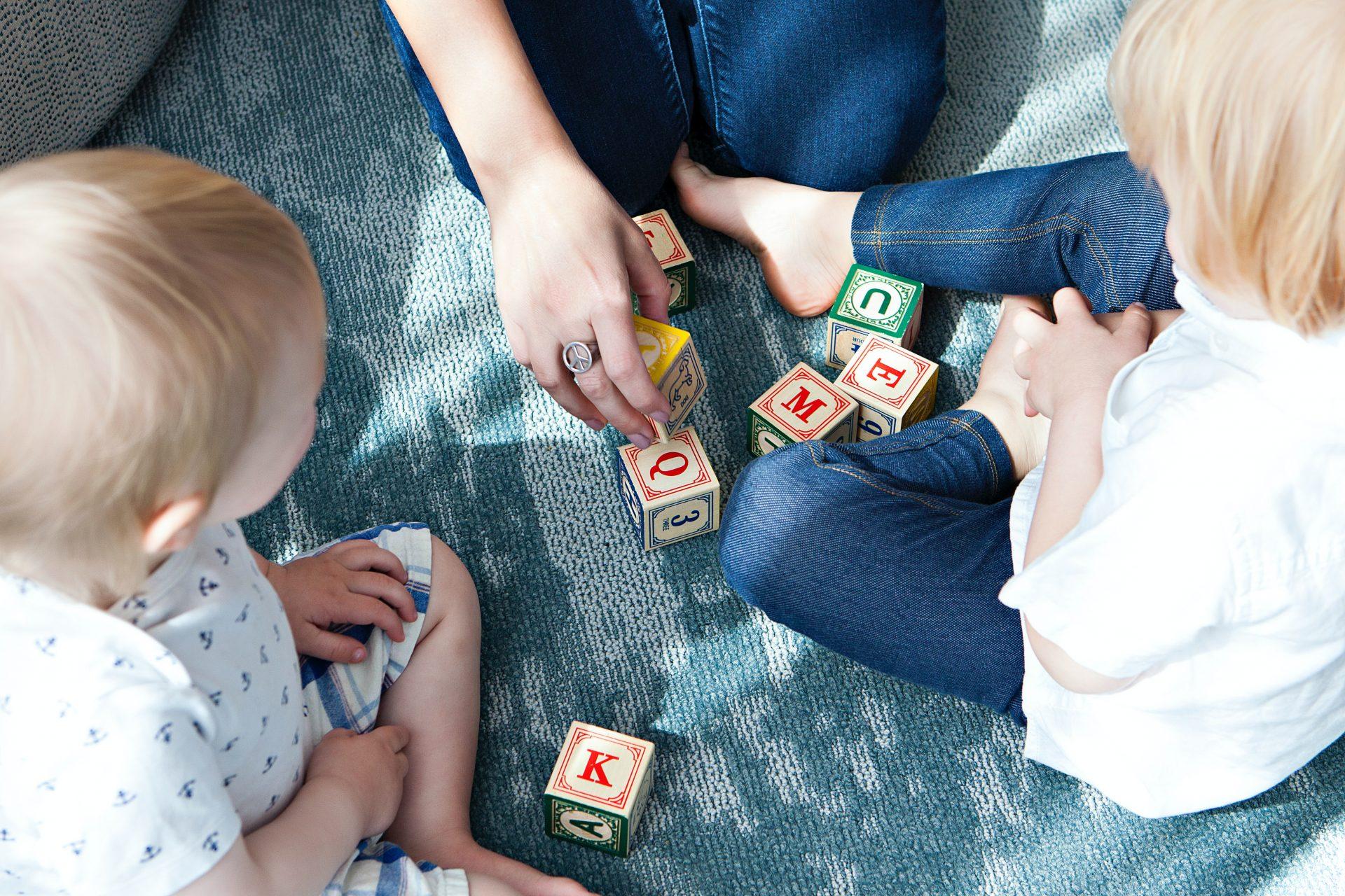 Zwei Kleinkinder spielen auf dem Boden mit Bauklötzen. Die Hände eines Erwachsenen sind zu sehen.