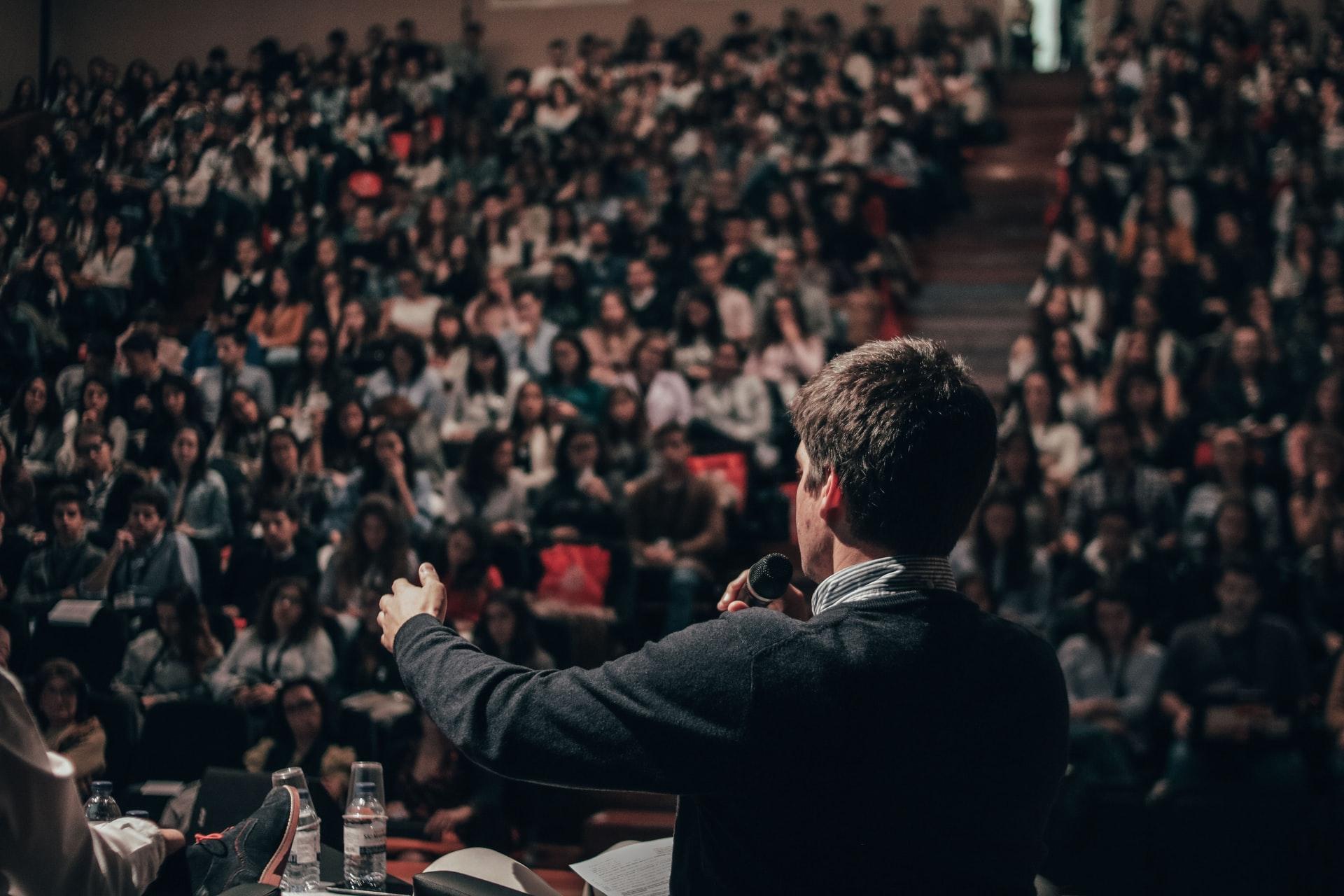 Ein Mann steht mit Mikrofon vor einem Publikum im Hörsaal und spricht mit anderen Personen auf der Bühne im Rahmen einer Podiumsdiskussion.