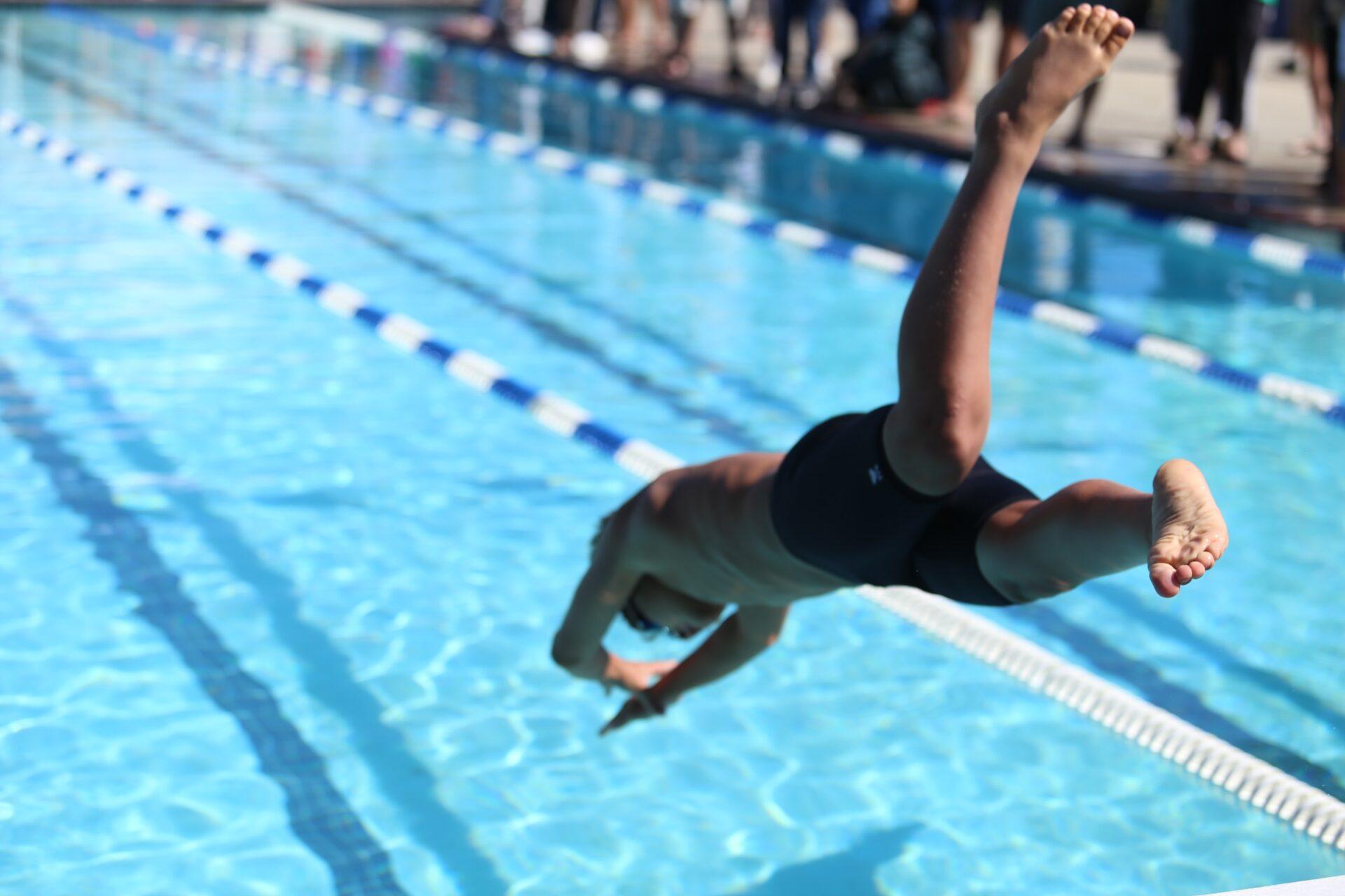 Ein Junge springt kopfüber in das Schwimmerbecken eines Freibads.
