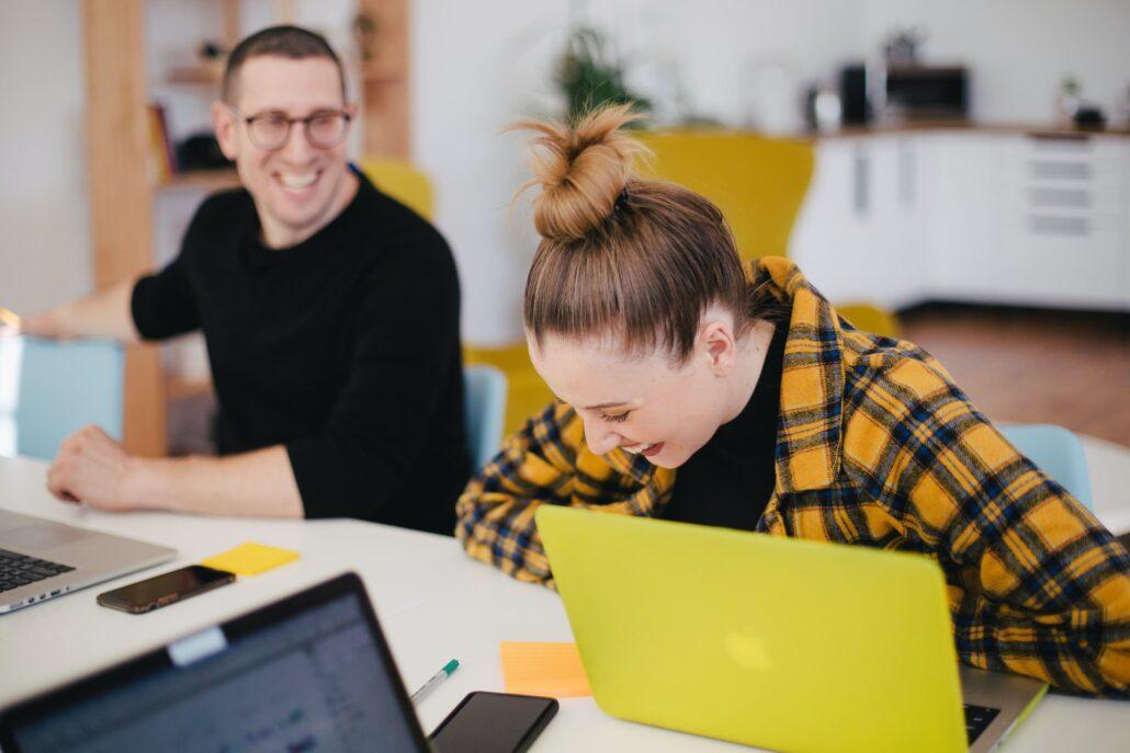 Zwei Menschen haben ein amüsantes Gespräch während eines Nutzertests eines digitalen Produkts.