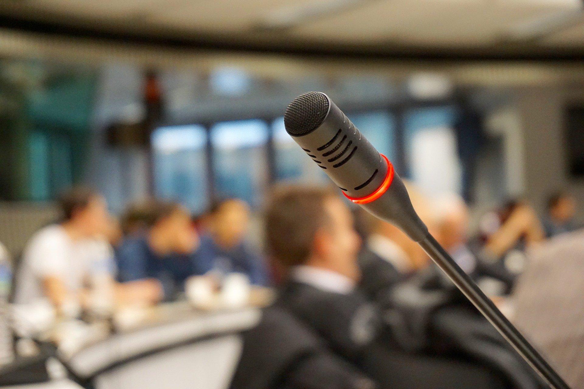 Im Vordergund ist ein eingeschaltete Rede-Mikrofon zu erkennen, im Hintergrund ein Plenum.